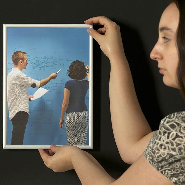 mujer-colgando-marco-sobre-pintura-super-magnetica