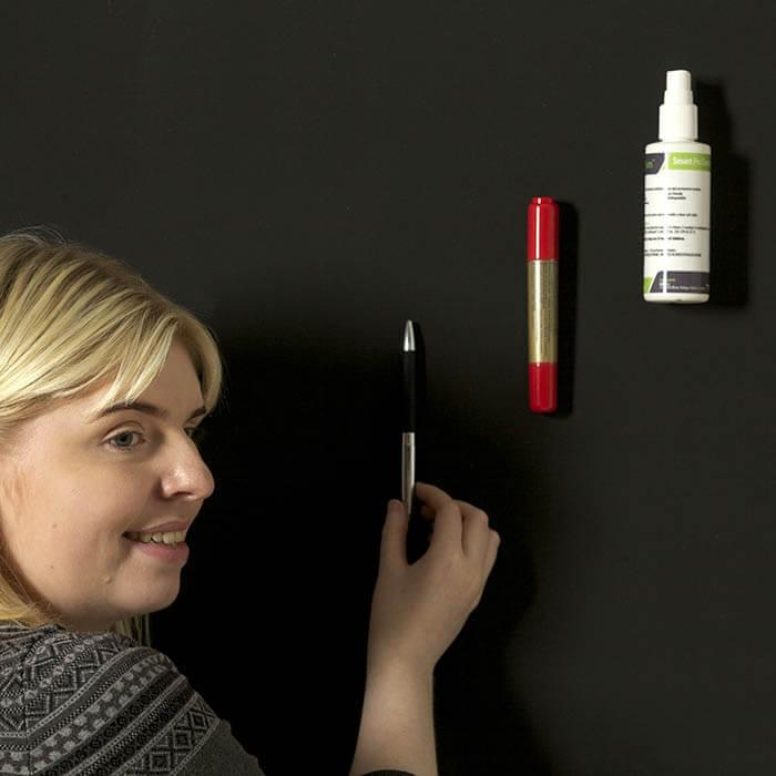 mujer-colgando-objetos-sobre-pintura-super-magnetica