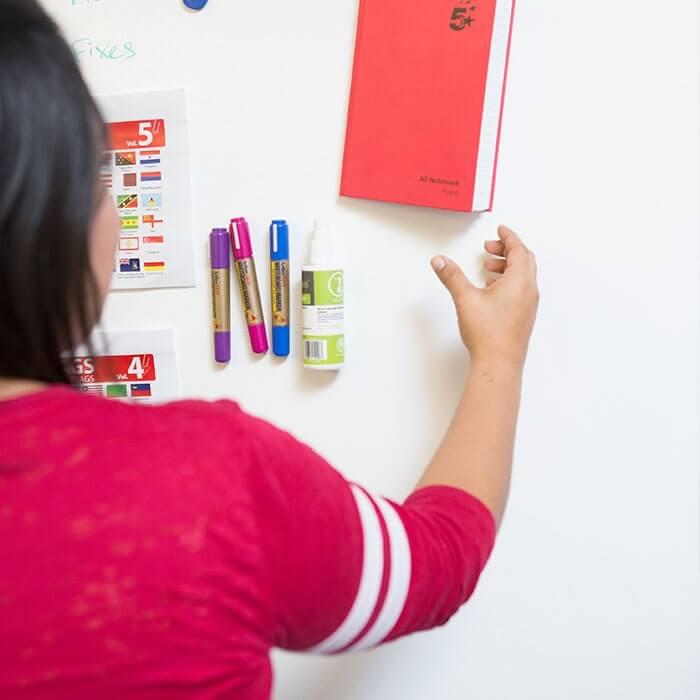 mujer-colgando-un-cuaderno-en-una-pared-magnetica-creada-con-yeso-magnetico